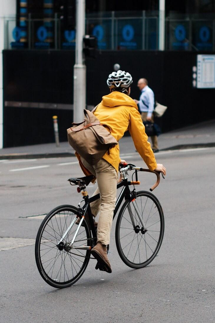 黄色いブルゾンを着て自転車に乗る男