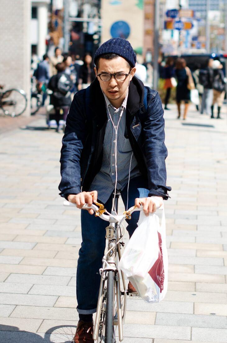 デニムジャケットを着て自転車に乗る男